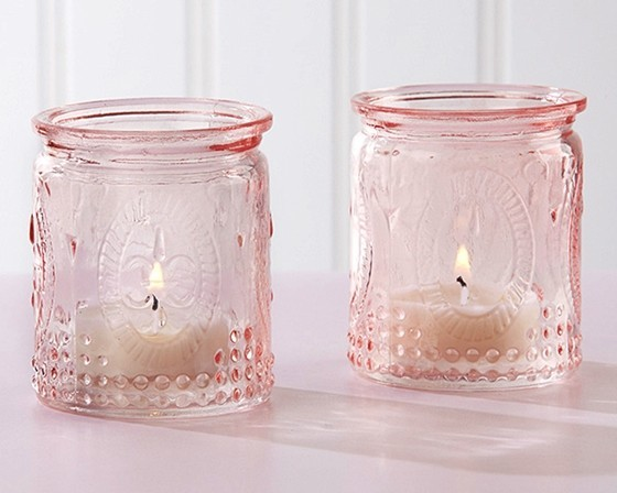 With a flame dancing inside, Kate Aspen's Vintage Pink Glass Tea Light Holder from the Modern Romance design collection brings that perfect romantic atmosphere to your wedding tables.